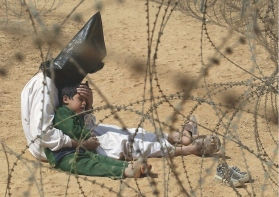 An Iraqi man comforts his four-year-old son at a holding center for prisoners of war, in the base camp of the US Army 101st Airborne Division near An Najaf. The boy had become terrified when, according to orders, his father was hooded and handcuffed. A soldier later severed the plastic handcuffs so that the man could comfort his child. Hoods were placed over detainees' heads because they were quicker to apply than blindfolds. The military said the bags were used to disorient prisoners and protect their identities. It is not known what happened to the man or the boy. (Jean-Marc Bouju)